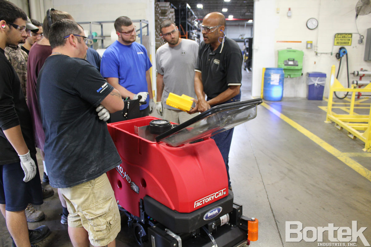 Sales representative trains factory employees to use Micro-HD scrubber