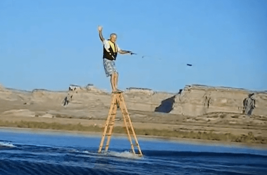 Leroy Wicklund wakeboards on ladder unsafely on top step.